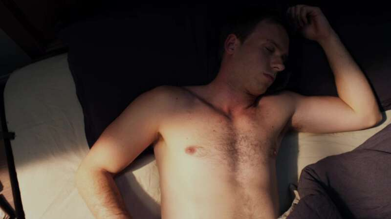 Shirtless actor Patrick J. Adams wakes up in bed